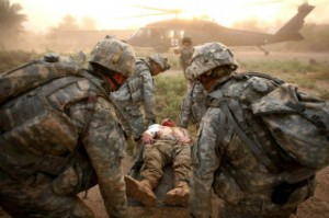 Soldiers attending to serious wounds in Iraq. We must pause to remember our servicemen and women's sacrifices.